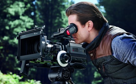 A man looking into the viewfinder of the Blackmagic URSA Mini cinema camera.