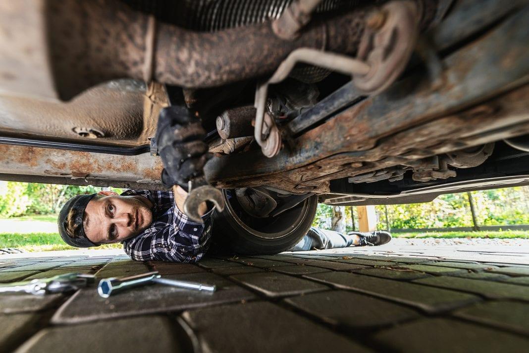 Man repairing rusty car